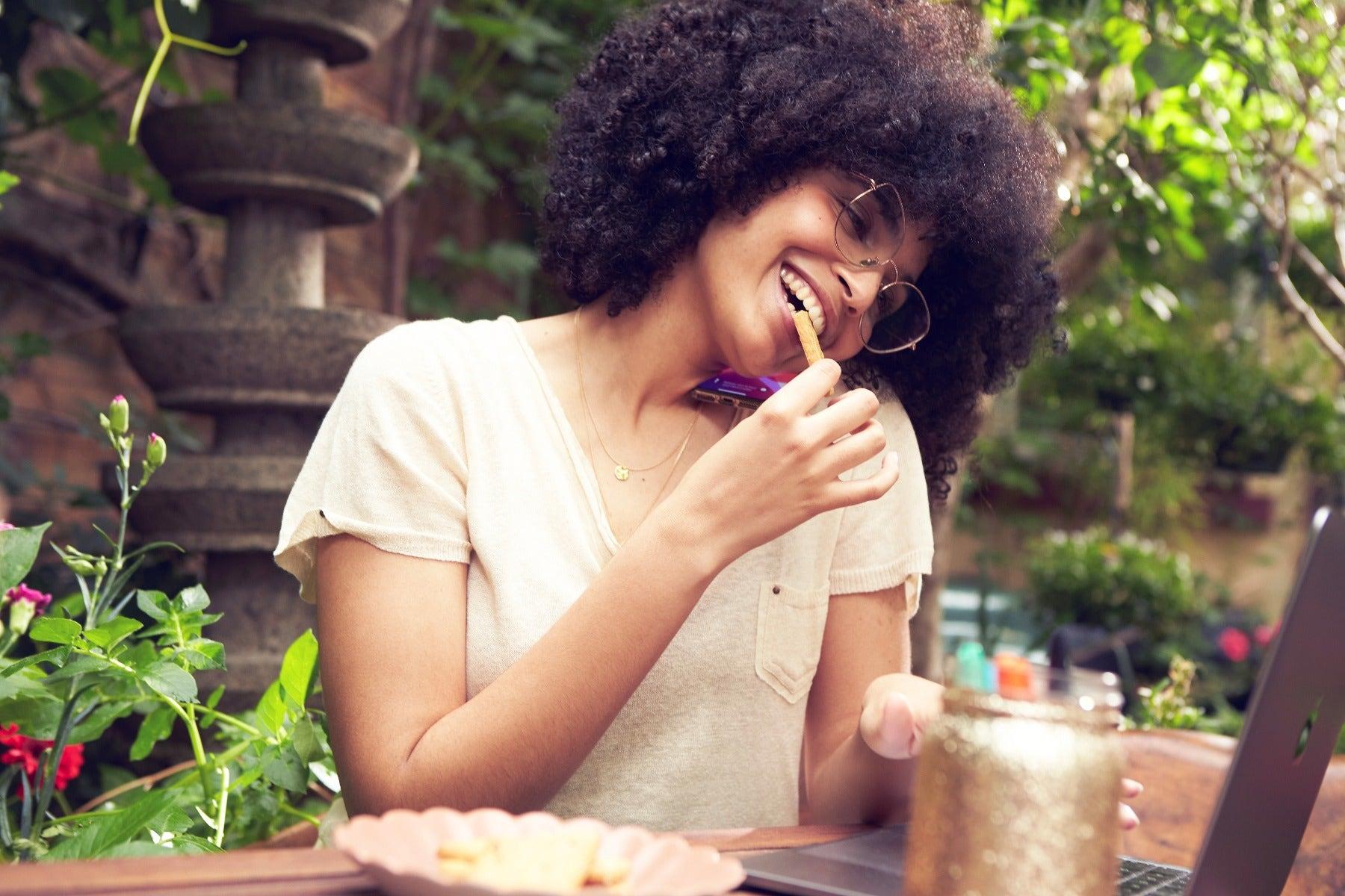 Femme qui mange un biscuit en terrasse