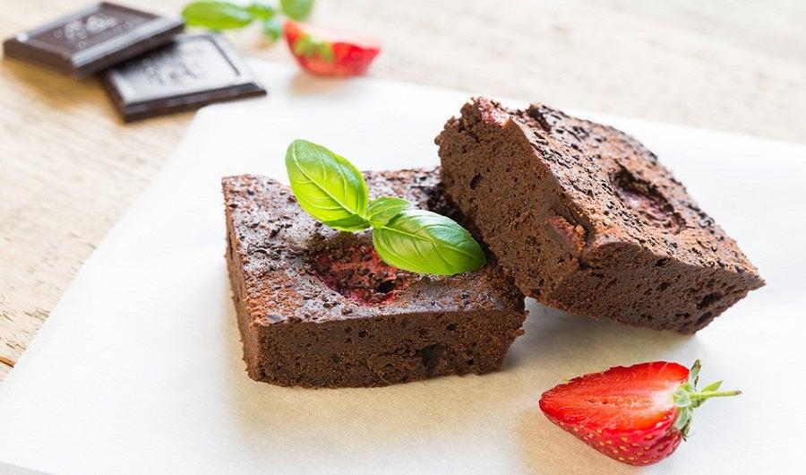 deux parts de brownie avec fraise coupée avec table en bois