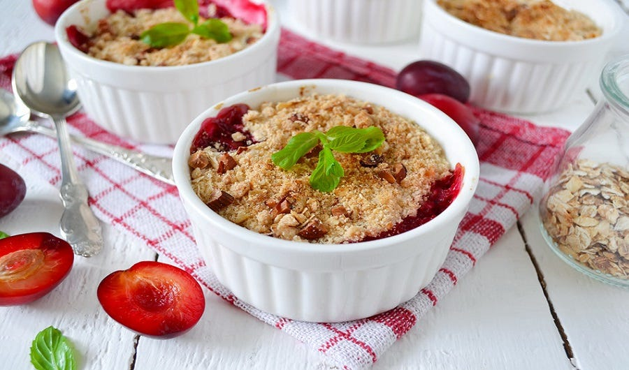 ramequin de crumble aux pommes et cranberries sur table blanche avec nappy Vichy