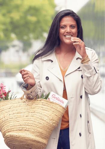 Femme qui goûte une barre-repas Gerlinéa en rentrant du marché