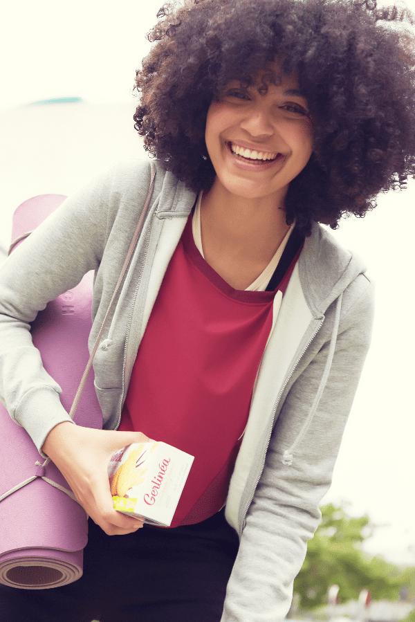 Femme tenant un paquet de biscuits Gerlinéa et un tapis de yoga