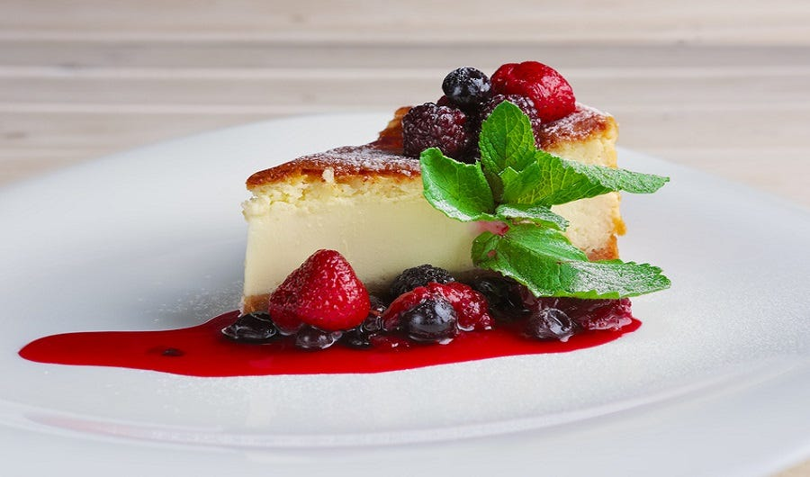 part de cheese-cake au citron et son coulis de fruits rouges sur assiette blanche