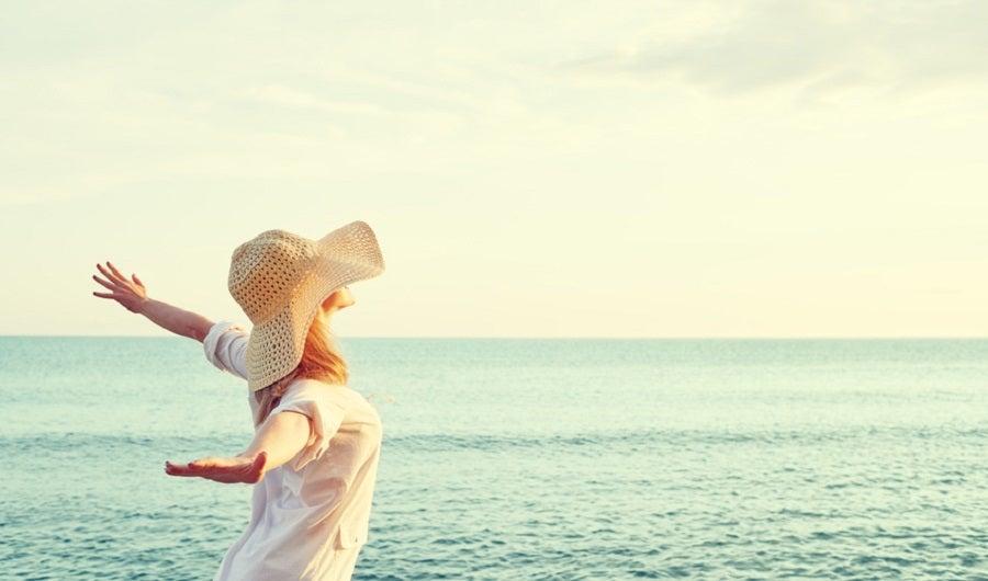 femme mince avec un chapeau de paille devant la plage