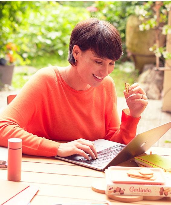 Femme travaillant sur son ordinateur portable tenant un biscuit Gerlinéa à la main