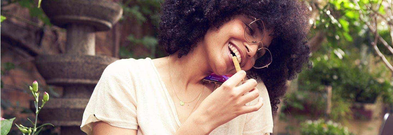 Femme qui mange une biscuit Gerlinéa tout en téléphonant sur une terrasse