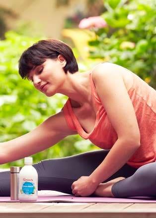 Femme en train de faire du yoga avec une bouteille d'Acqua Drainer à portée de main