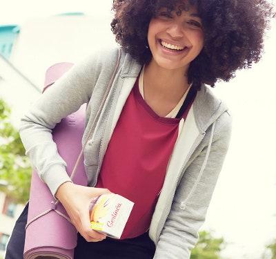 Femme souriante tenant un paquet de biscuit Gerlinéa et un tapis de yoga
