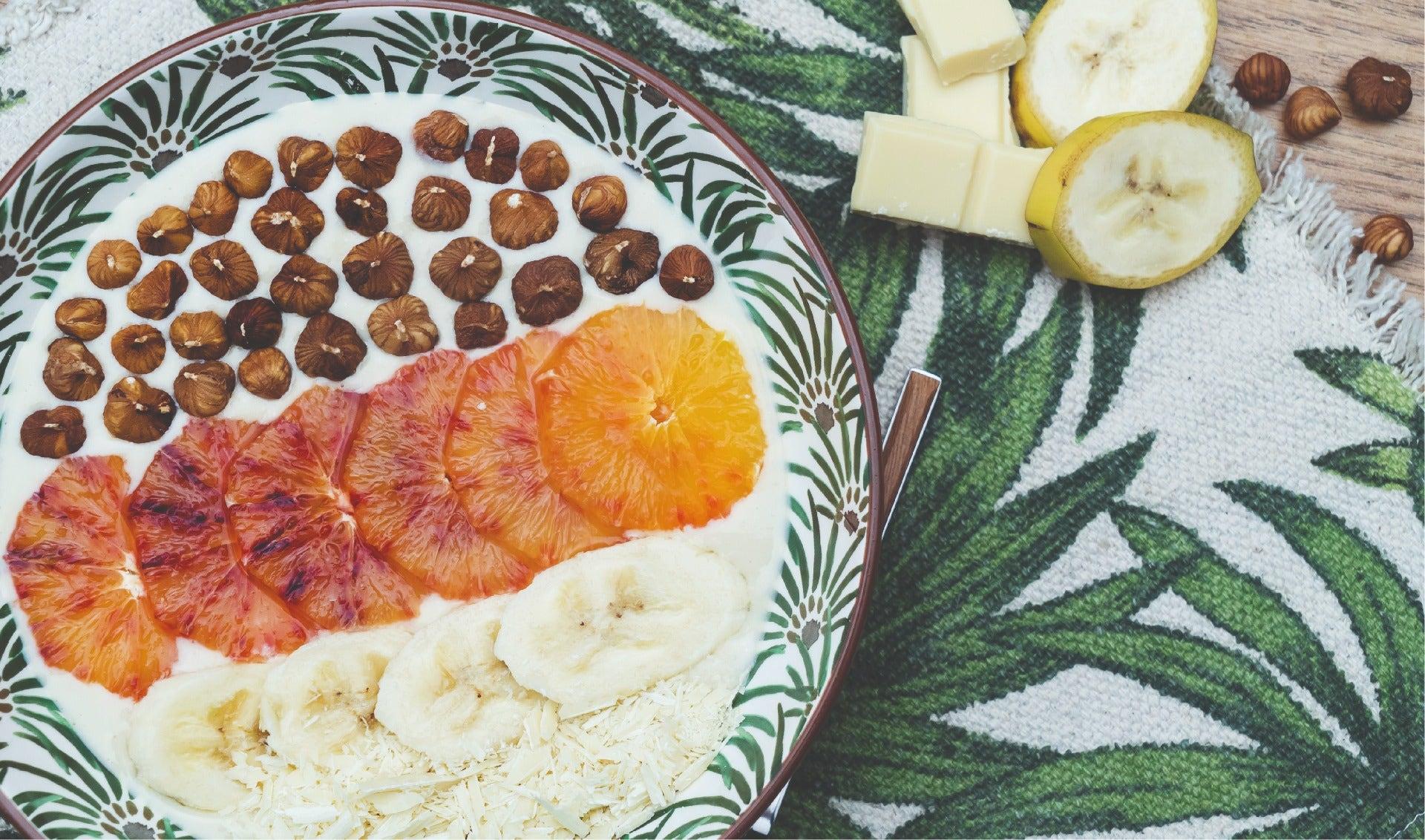 Assiette de crème vanillée avec des rondelles de bananes, d'orange sanguine et d'éclats de noisette