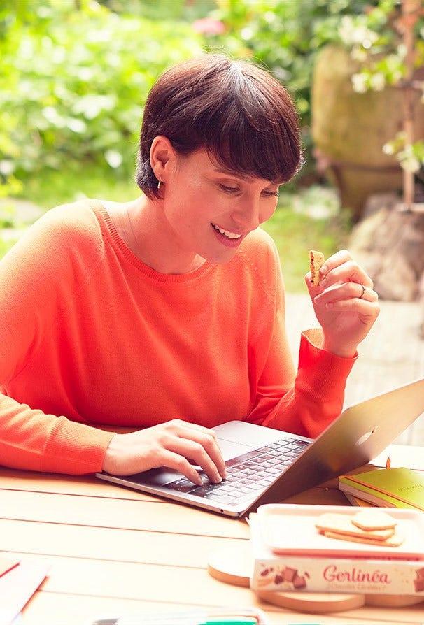 Femme travaillant sur son ordinateur portable tout en mangeant un biscuit Gerlinéa
